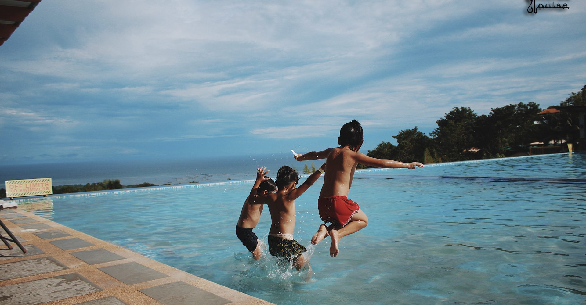 boys jumping into a pool